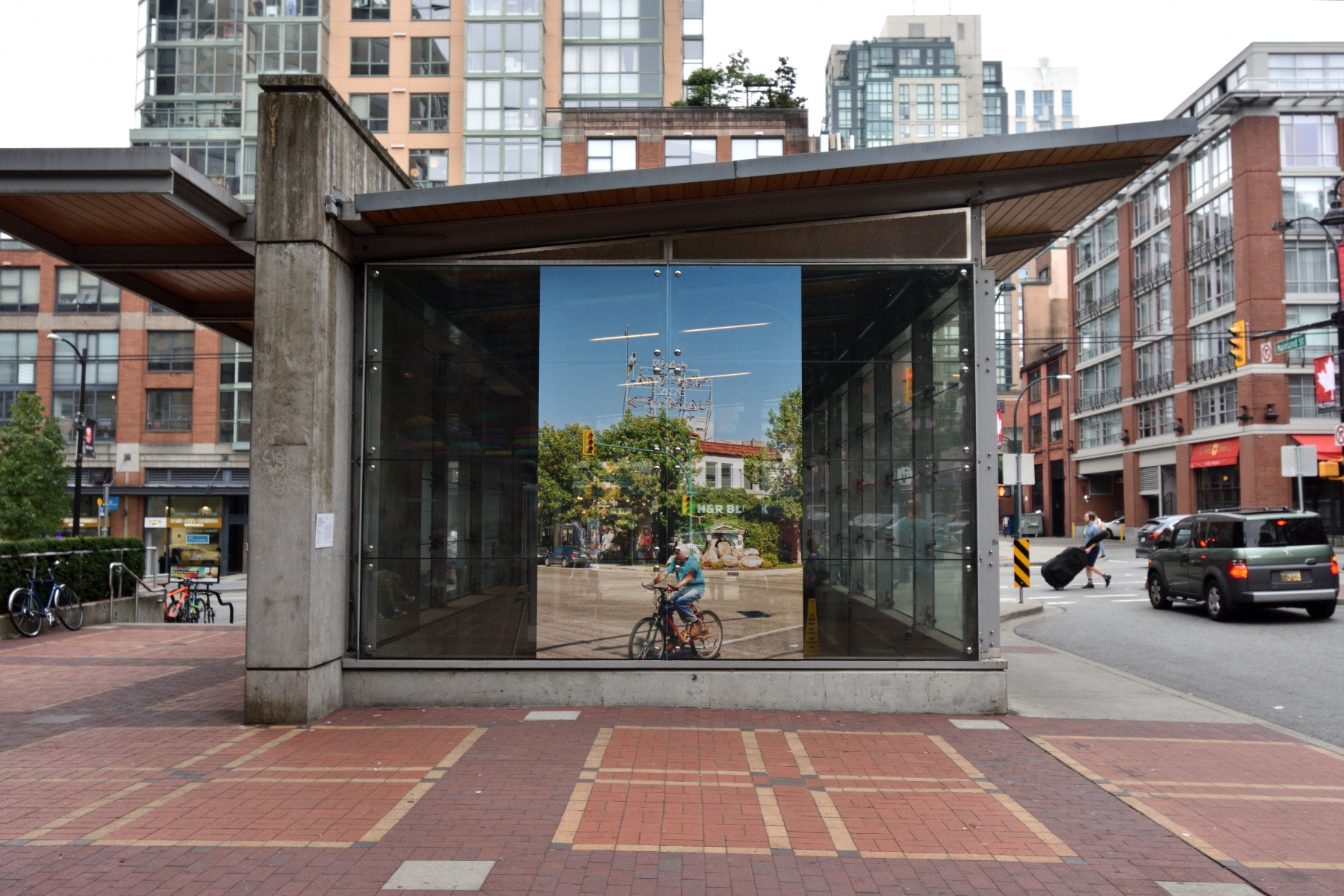 A colour photographic print is presented on the glass face of the SkyTrain station facade. Around the station, the surrounding environment (condo buildings, cars on the street, bricked pathways, grey sky) can be seen.